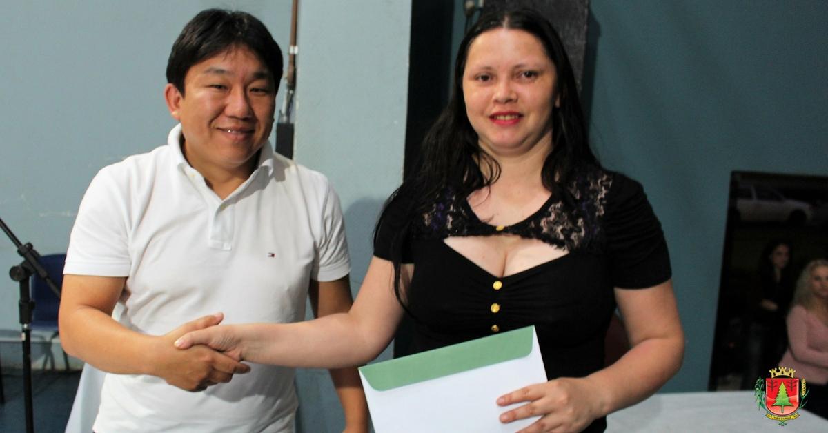 Vice-prefeito Gilson Nagano fazendo a entrega de título a moradora.